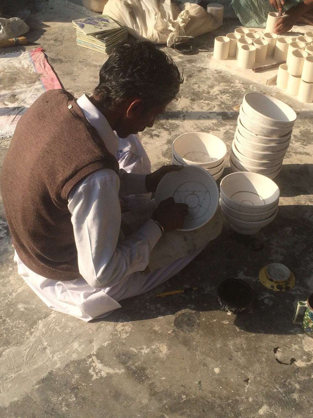 Hand drawing the designs on the pottery.
