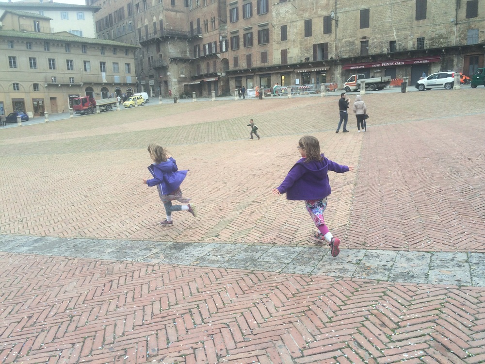 Running around in the historic, medevil Piazza del Campo