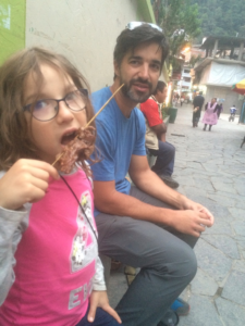 Eating grilled meat on a stick in Aguas Calientes, Peru